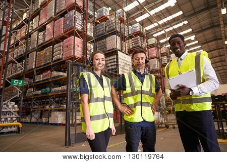 Distribution warehouse manager and colleagues look to camera