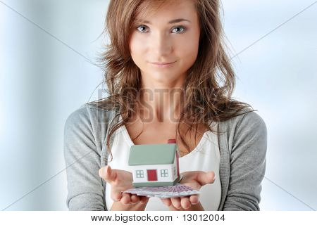 Beautiful young woman holding euros bills and house model over white - real estate loan concept
