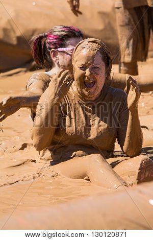 HAMPTON, GA - APRIL 2016: A woman covered in mud laughs after sliding into a pit of muddy water at the Dirty Girl Mud Run obstacle course event in Hampton GA on April 23 2016 .