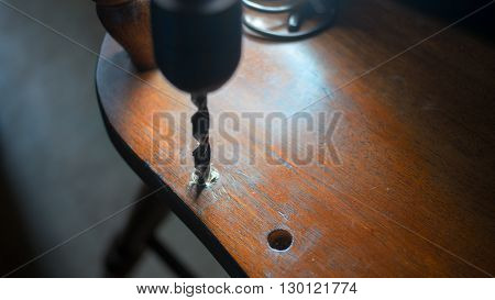 Drilling. Carpenter repairing old chair. Selective focus on drill, shallow dof.