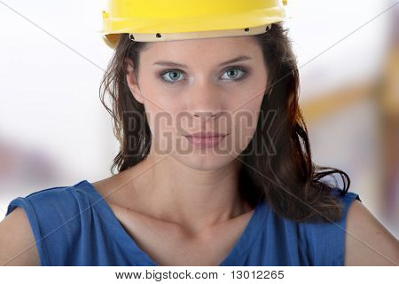 Young female architect or builder wearing a yellow hart hat on a construction site