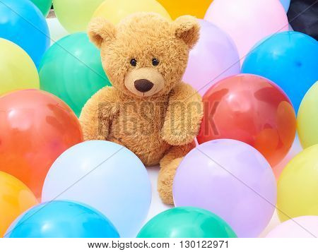 Teddy bear in colourful balloons closeup.Background of many colorful balloons.