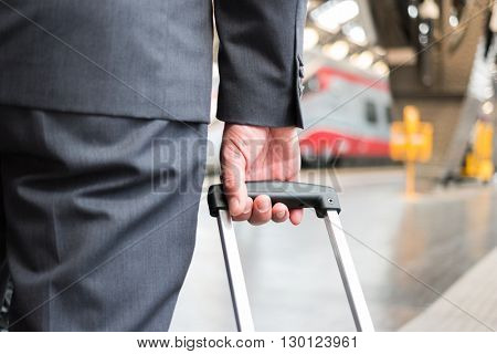 Detail of a businessman pulling a trolley in a train station