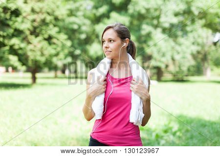 Active woman relaxing after running in a park