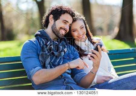 Young couple looking at a smartphone together on a bench in the park