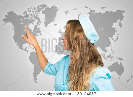 Portrait of a smiling stewardess in front of a world map