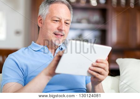 Portrait of a smiling mature man using his digital tablet while sitting on the couch