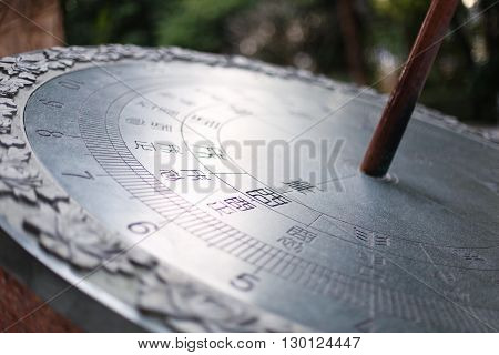 Silver sundial. Beautifully shining in the park.