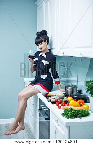 Young slim girl in the kitchen. The girl is drinking wine. In the foreground of the future dinner. Household chores.