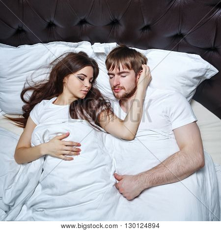 Married couple sleeping in bed. Sweet dreams. Marital bed. Wife hugging her husband in a dream.