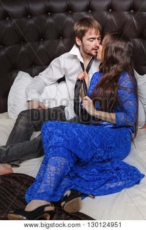 Married couple. Romantic evening at the hotel. Love and passion. Girl holds her husband's tie and kisses.