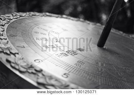 Large metal sundial with Chinese characters. Big watches.