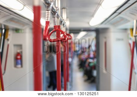 Inside the subway car. Red handrails in the subway.