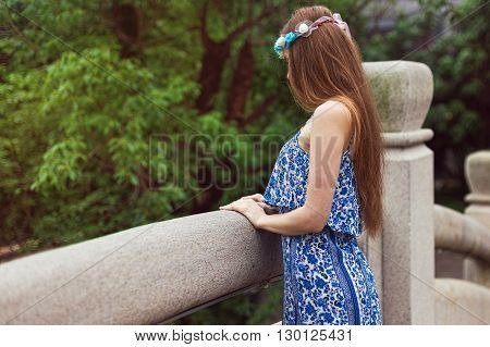 A young girl stands on a bridge on a background of green trees and looks down. The girl turned sideways.