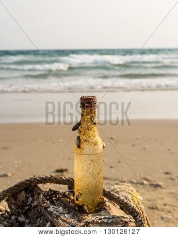 Old disused beverage bottle on the beach at the seaside