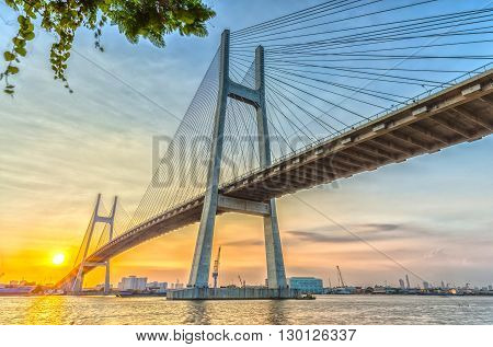 Ho Chi Minh city, Vietnam - January 14th, 2016: Sunset bridge with steel wire radiating sun rays under bridge highlighting beauty connecting two banks on Saigon River Ho Chi Minh City, Vietnam