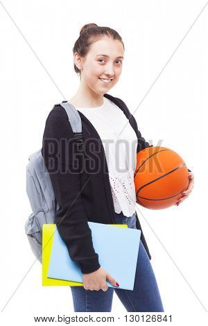 Cute young student girl holding colorful notebooks and a basketball, isolated on white background
