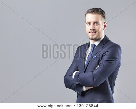 Portrait of a happy smiling businessman on grey background