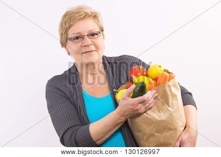 Happy smiling elderly senior woman holding shopping bag with fruits and vegetables healthy nutrition in old age