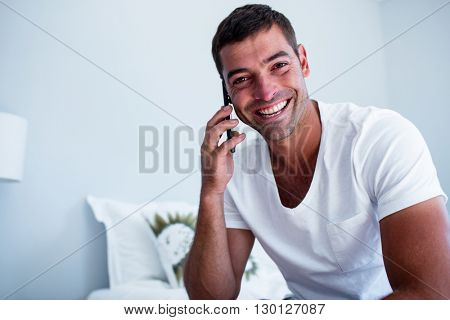 Portrait of man talking on phone in bedroom