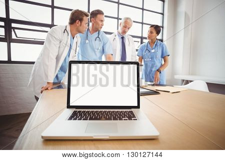Laptop on table in conference room and medical team interacting in background