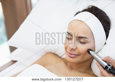 Close-up of topless woman receiving facial massage at spa