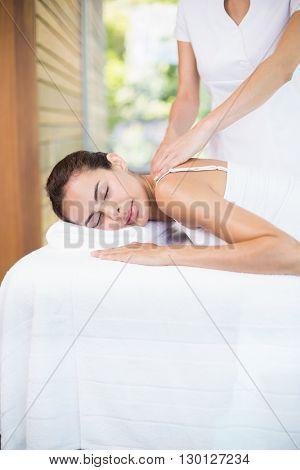 Female masseur massaging beautiful woman at health spa