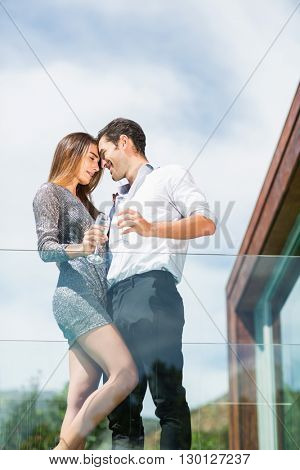 Low angle view of romantic couple with champagne at balcony in resort