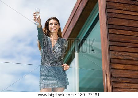 Low angle view of gorgeuos woman showing champagne flute while standing by glass railing at balcony