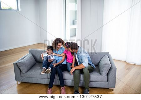Happy family sitting together on sofa in living room