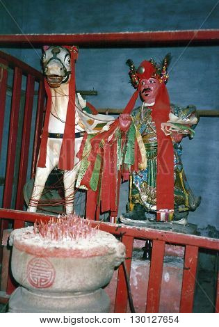 MACAU - CIRCA 1987: Sacred images of a man and a horse inside the Kun Iam Buddhist Temple in Macau.