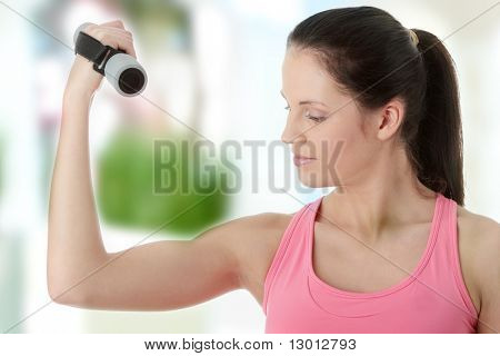 Beautiful young woman doing exercise with dumb bells