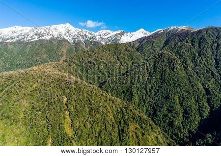 Aerial view of New Zealand mountains. View from above on snow caped mountains with green forest over slopes. New Zealand wilderness landscape of Price range with mount Cloher and Gunn Peak