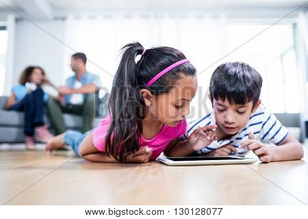 Brother using digital tablet while parents sitting on sofa in background