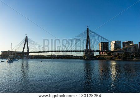 ANZAC Bridge with australian flags and Sydney CBD cityscape at dusk Sydney NSW Australia