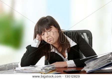 Female executive filling out tax forms while sitting at her desk.
