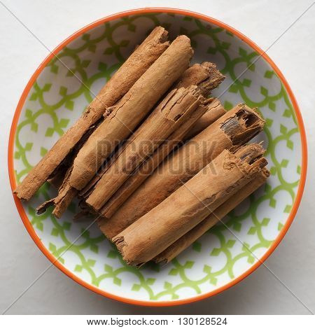 Dried Cinnamon sticks / quills / bark in a small colorful ceramic bowl.