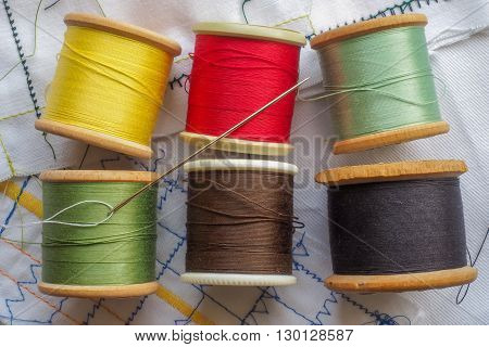 A variety of colored cottons on spools. with a sewing needle.