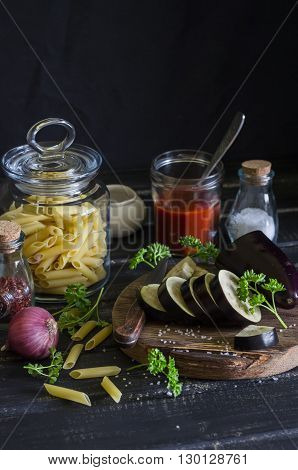 Raw ingredients for cooking Italian pasta with eggplant - penne pasta eggplant onion tomato sauce spices and herbs. On a dark wooden background. Healthy vegetarian food