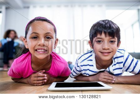 Portrait of brother and sister lying on floor with digital tablet in living room