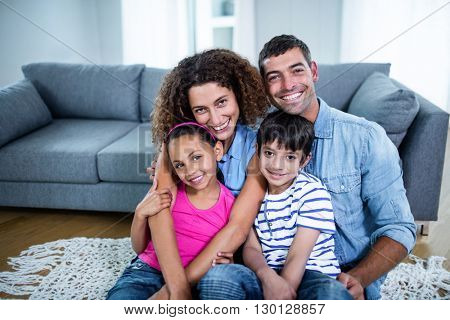Portrait of happy family sitting together on floor in living room