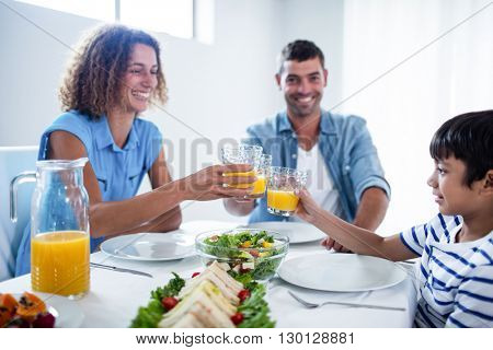 Family toasting glasses of orange juice while having breakfast at home