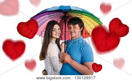 Happy smiling couple under colorful umbrella and falling red hearts