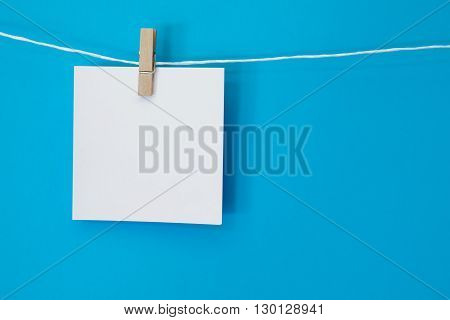 A bright white blank note square hanging on a white string line in front of a bright blue colored background.