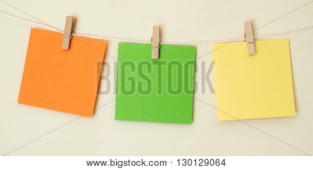 Three brightly colored note squares hanging on a white string line in front of a pale cream background.