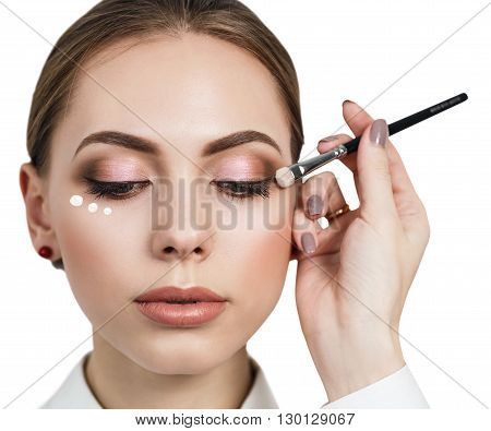 Beautiful woman face with make-up and cream dotts on a cheek. Skin care concept. Closeup portrait isolated on white.
