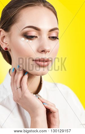 Close-up portrait of beautiful woman face with cream dotts isolated on white
