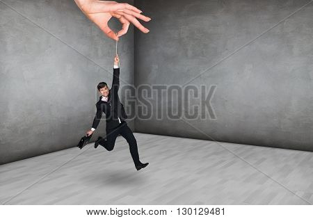 Big hand holds businessman in rough gray room
