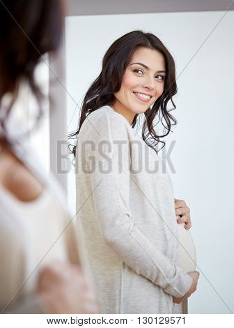pregnancy, motherhood, people and expectation concept - happy pregnant woman looking to mirror at home