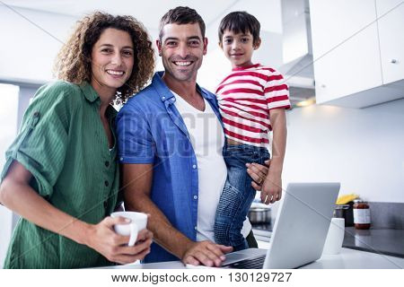Parents using laptop with son in kitchen at home